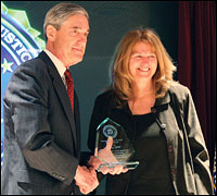 Phtograph: Director Mueller presents Patsy Spier with the 'Strength of the Human Spirit Award' for her resilience following a 2002 attack that killed her husband