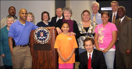 Carlie Shockey (front row, middle), along with her mom and sister (second, second and third from right), during her recent visit with some of the Kansas City employees who worked on her kidnapping case 10 years ago.