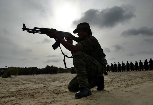 A woman fighter of the Tamil Tigers takes a shooting position in Sri Lanka, July 2007. AP Photo.