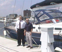 Photograph of two men standing in front of a yacht.