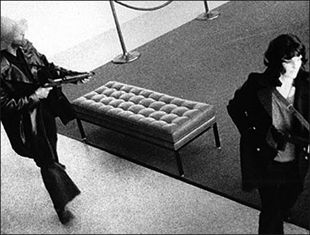 Assault rifle in hand, Hearst joins DeFreeze in robbing a San Franciso bank on April 15, 1974. It was her first crime as a professed SLA member.