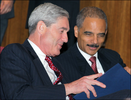 Director Mueller talks with Attorney General Holder (right) before the ceremony.