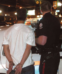 Photograph of a police officer with a handcuffed young man who has been arrested.
