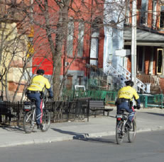 Picture of police officers patroling on bicyles down a neighborhood street.