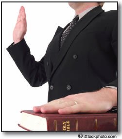 Man taking an oath with his right hand raised and his left hand on the Bible.