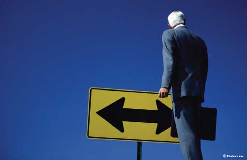 Stock image of a businessman looking at a road sign with an arrow pointing left and right.