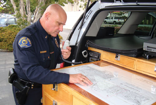 Police officer using police radio and looking at map.