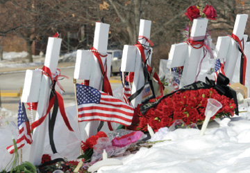 Photograph of white crosses with flowers and U.S. flags memorializing students shot on a university campus.