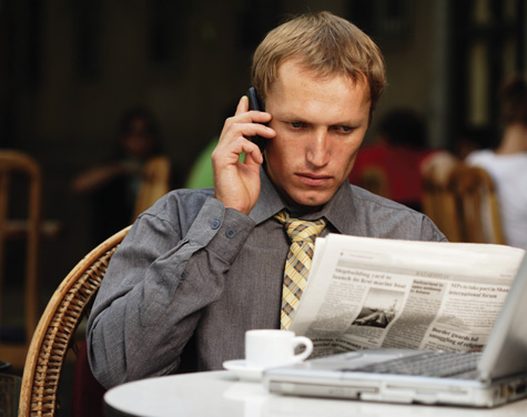 photograph of a man talking on the phone and reading a newspaper at a table