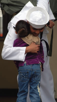 Navy officer hugs child