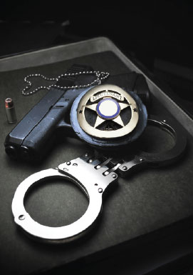 photograph of a gun with a badge and hand cuffs