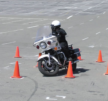 Picture of police officer on motorcycle training around cones.