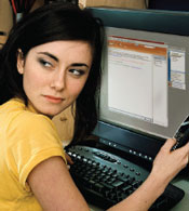Photograph of young girl at computer looking guiltily over her shoulder.