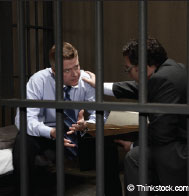 photograph of man with counsel behind bars